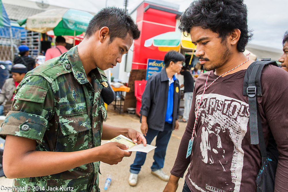 09 JULY 2014 - ARANYAPRATHET, SA KAEO, THAILAND:  A Thai soldier checks the documents of a Cambodian migrant worker at the Thai Immigration One Stop Service Center in Aranyaprathet on the Thai-Cambodian border. More than 200,000 Cambodian migrant workers, most undocumented, fled Thailand in early June fearing a crackdown by Thai authorities after a coup unseated the elected government. Employers have been unable to fill the vacancies created by the Cambodian exodus and the Thai government has allowed them to return. The Cambodian workers have to have a job and their employers have to vouch for them. The Thai government is issuing temporary ID cards to allow them to travel openly to their jobs. About 800 Cambodian workers came back to Thailand through the Aranyaprathet border crossing Wednesday. The Thai government has opening similar service centers at three other crossing points on the Thai-Cambodian border.   PHOTO BY JACK KURTZ