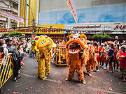 """19 FEBRUARY 2015 - BANGKOK, THAILAND:  Lion dancers perform for Chinese New Year on Yaowarat Road in Bangkok. 2015 is the Year of Goat in the Chinese zodiac. The Goat is the eighth sign in Chinese astrology and """"8"""" is considered to be a lucky number. It symbolizes wisdom, fortune and prosperity. Ethnic Chinese make up nearly 15% of the Thai population. Chinese New Year (also called Tet or Lunar New Year) is widely celebrated in Thailand, especially in urban areas that have large Chinese populations.   PHOTO BY JACK KURTZ"""