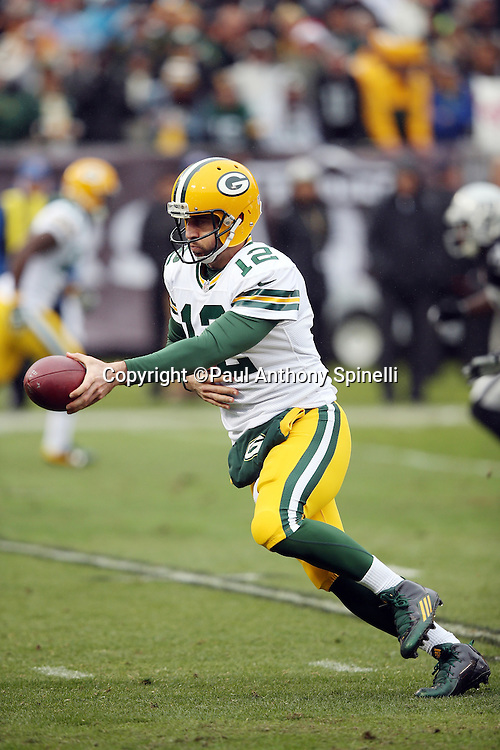 Green Bay Packers quarterback Aaron Rodgers (12) hands off the ball on a second quarter running play during the 2015 week 15 regular season NFL football game against the Oakland Raiders on Sunday, Dec. 20, 2015 in Oakland, Calif. The Packers won the game 30-20. (©Paul Anthony Spinelli)