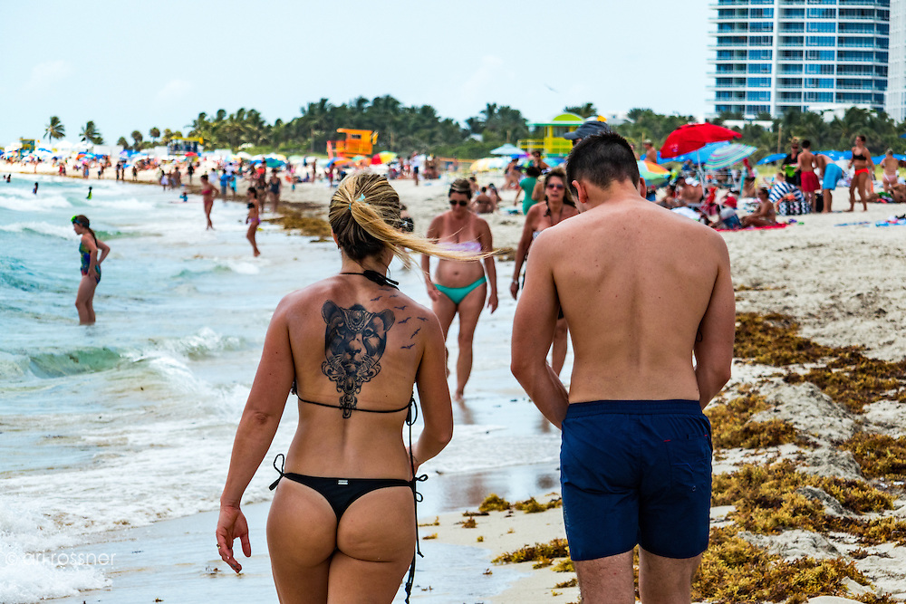 Woman with a large lion face tatoo on her back walking on the beach in South Miami Beach