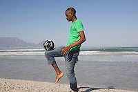 Young man playing soccer on beach