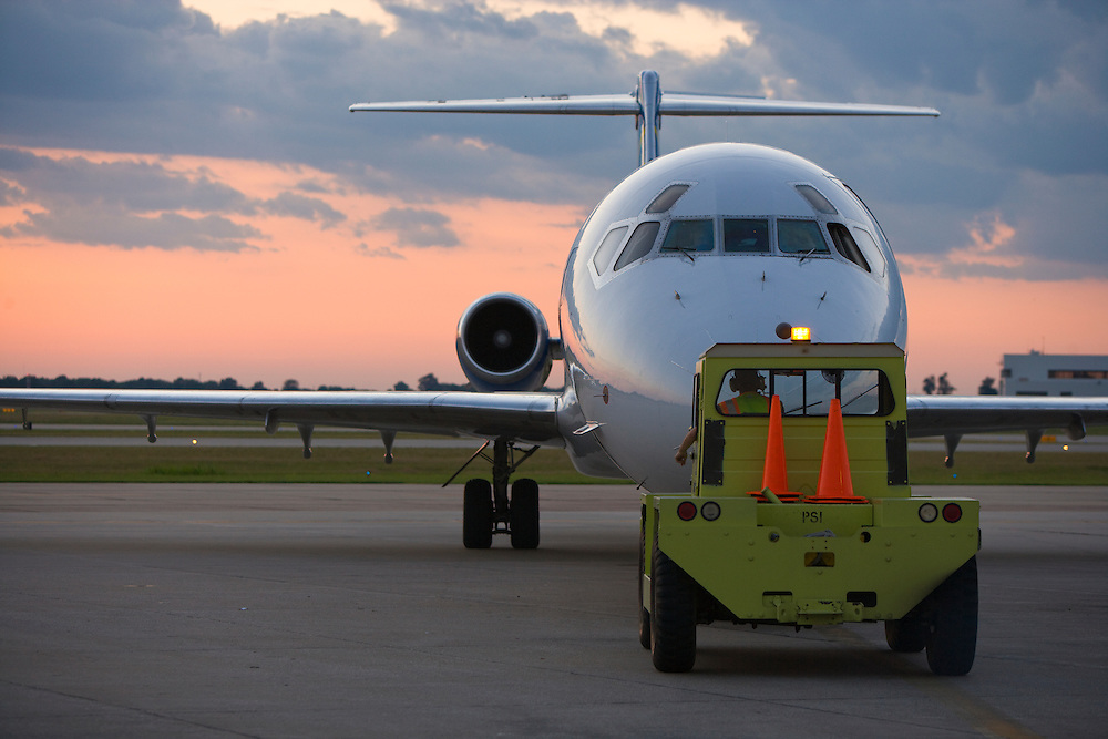 A commercial jet airplane is backed out of the gate in preparation for take-off during a sunset.