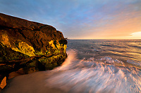 I took this bizarre image of a wave crashing against mossy rocks in this San Diego coast sunset photograph.