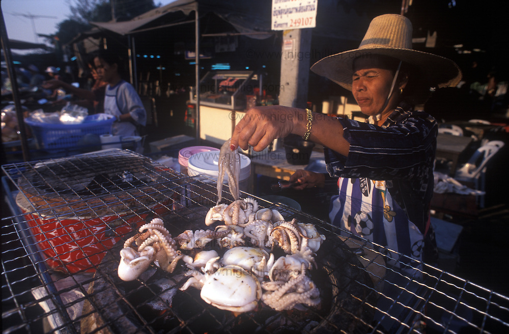 woman barbecueing squid, thailand