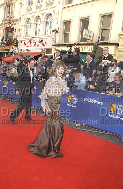 Joan Collins and Percy Gibson. TV Bafta Awards. 21 April 2002. © Copyright Photograph by Dafydd Jones 66 Stockwell Park Rd. London SW9 0DA Tel 020 7733 0108 www.dafjones.com