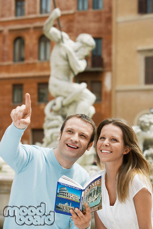 Young couple with guidebook looking at monuments on street in Rome Italy head and shoulders