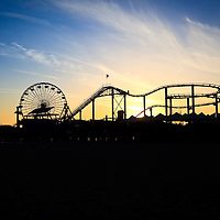 Photo of Santa Monica Pier sunset. Santa Monica Pier is a landmark that has an amusement park with a ferris wheel, roller coaster, restaurants, and other attractions.