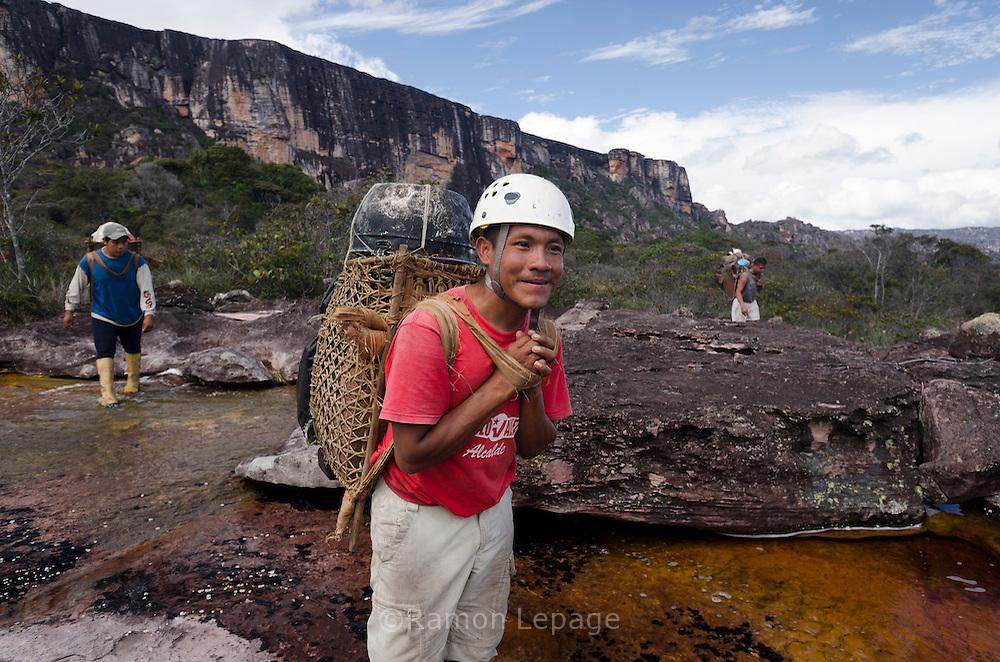 """AUYANTEPUY, VENEZUELA. Porteadores Pemon llevando  parte de la carga en sus Guayares. El Auyantepuy es el mayor de los tepuis del Parque Nacional Canaima. En sus 700 kms2 alberga el salto angel o conocido por lengua indígena Pemon como """"Kerepacupai Vena; es la caída de agua más grande del mundo con sus 979 metros de altura. (Ramon lepage /Orinoquiaphoto/LatinContent/Getty Images)"""