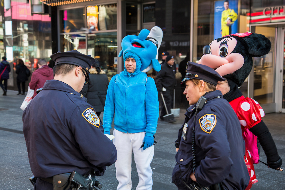 Two New York Police Officers interview two people dressed as life-size Smurf and Minnie Mouse on Time Square, Midtown Manhattan, New York City, New York, United States.  In 2016, Mayor de Blasio signed a law to declare pedestrian plazas, like Times Square to be no-soliciting zones due to the ongoing issues of costume characters harassing tourists for money. <br /> (photo by Andrew Aitchison / In pictures via Getty Images)