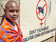 Simanga Kolii, a student at Engkiteng Lepa School in Maji Moto, with the school's motto.