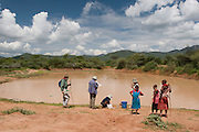 Earthwatch volunteers collect water sample data at a small dam in Samburu district, Kenya, while local girls observe.
