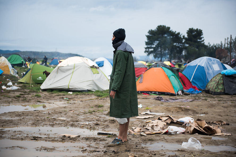 A man stands in muddy field at the transit camp of Idomeni, Greece. <br /> <br /> Thousands of refugees are stranded in Idomeni unable to cross the border. The facilities are stretched to the limit and the conditions are appalling.