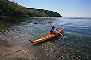 Man in kayak paddles onto placid Lake Superior from stony beach at Terrace Bay, Ontario; Canada.