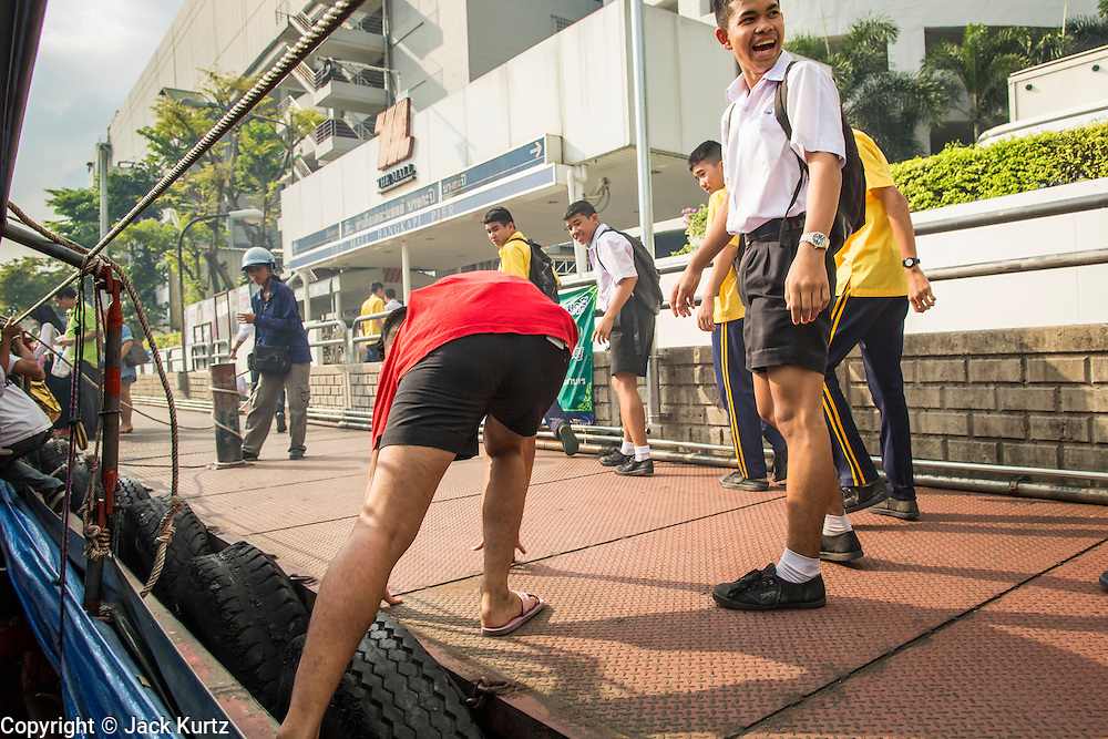 14 NOVEMBER 2012 - BANGKOK, THAILAND: School boys laugh when one of their friends gets tripped in the ropes of a passenger boat while they get off the khlong boat at the Bangkapi Mall Pier on Khlong Saen Saeb. Bangkapi Mall is one of the larger malls in Bangkok and the only with direct access to the khlong boats, although there are piers close the malls in central Bangkok. Bangkok used to be criss crossed by canals (called Khlongs in Thai) but most have been filled in and paved over. Khlong Saen Saeb is one of the few remaining khlongs in Bangkok with regular passenger boat service. Boats and ships play an important in daily life in Bangkok. Thousands of people commute to work daily on the Chao Phraya Express Boats and fast boats that ply Khlong Saen Saeb. Boats are used to haul commodities through the city to deep water ports for export.      PHOTO BY JACK KURTZ