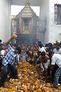 Breaking coconuts in front of the Vel cart or Chariot before it begins its journey around the temple precinct.