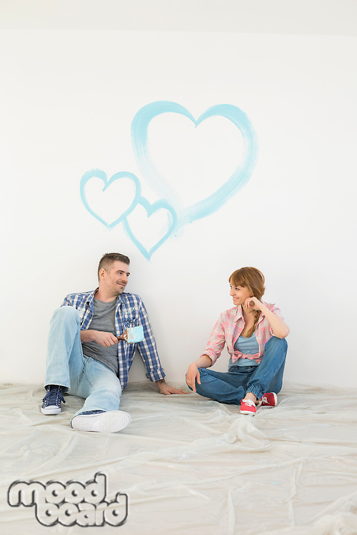 Full-length of mid-adult couple with painted hearts on wall