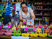 "03 NOVEMBER 2017 - BANGKOK, THAILAND: A woman makes and sells krathongs during Loi Krathong at Wat Prayurawongsawat on the Thonburi side of the Chao Phraya River. Loi Krathong is translated as ""to float (Loi) a basket (Krathong)"", and comes from the tradition of making krathong or buoyant, decorated baskets, which are then floated on a river to make merit. On the night of the full moon of the 12th lunar month (usually November), Thais launch their krathong on a river, canal or a pond, making a wish as they do so. Loi Krathong is also celebrated in other Theravada Buddhist countries like Myanmar, where it is called the Tazaungdaing Festival, and Cambodia, where it is called Bon Om Tuk.     PHOTO BY JACK KURTZ"