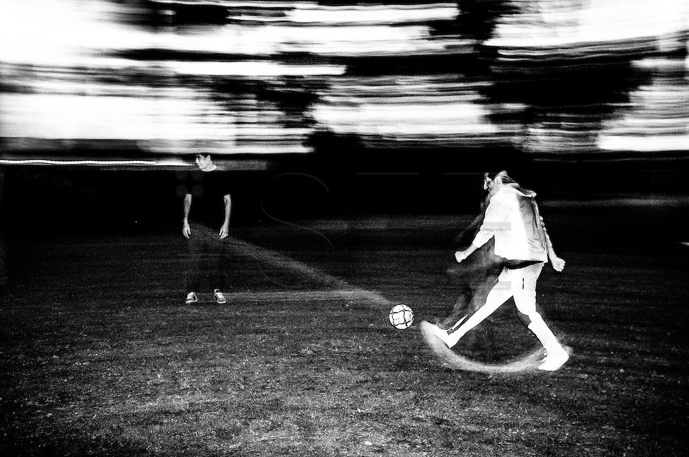 Two Afghan men are playing football with a group of men and international volunteers at night after dinner. FEDASIL Rixensart asylum center. Rixensart, Belgium. April 2015. I took these photographs during an international volunteer program that I liderate with an international volunteering group.