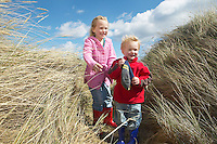 Brother and sister (4-6) standing among long grass