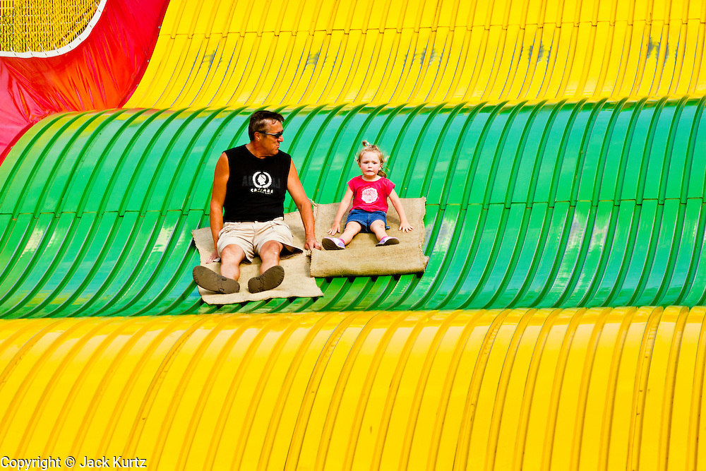 "01 SEPTEMBER 2011 - ST. PAUL, MN:  A father and daughter ride the Giant Slide at the Minnesota State Fair. The Minnesota State Fair is one of the largest state fairs in the United States. It's called ""the Great Minnesota Get Together"" and includes numerous agricultural exhibits, a vast midway with rides and games, horse shows and rodeos. Nearly two million people a year visit the fair, which is located in St. Paul.   PHOTO BY JACK KURTZ"