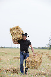 cowboy working on a ranch with hay bales