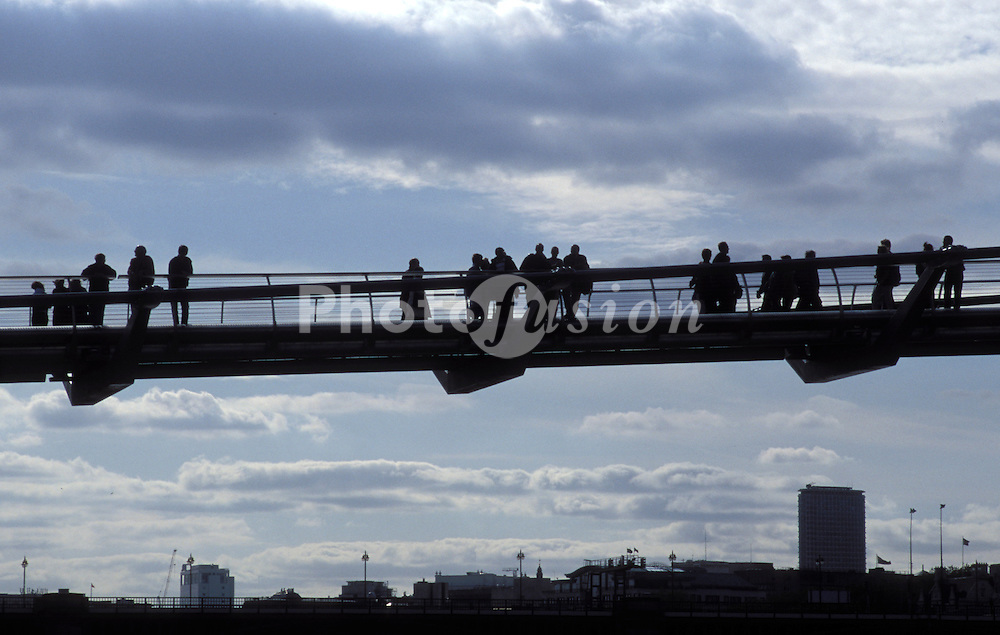 Silhouette of people walking on Millennium Bridge over River Thames on its first weekend of opening; Bankside; June 2000 London UK