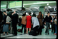 Travelers wait on platform below hourly schedule for bullet train (Shinkansen) in Tokyo Station. Japan