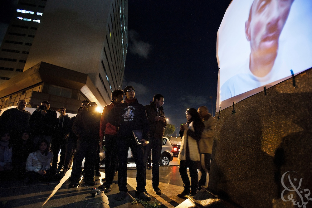 "Mustafa Kandil  (c, glasses) and others stand near as an anti-military film is shown on a makeshift screen taped to a statue January 19, 2012 in Cairo during an an""Askar kazeboon"" public video screening. Called ""Kazeboon"" for short, meaning ""liars"" in Arabic, it is a public grassroots campaign in Egypt at exposing what protestors say is the lies and propoganda of the ruling Supreme Council of Armed Forces (SCAF). The group shows their short anti-military films in public places to help promote the young activists and their goal of continuing the revolution in Egypt that was started last year."