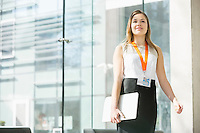 Smiling businesswoman holding laptop while standing in office
