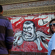 Bystanders look at a satirical graffiti of president Morsi, outside the presidential Palace in central Cairo.