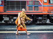 16 APRIL 2014 - BANGKOK, THAILAND: A Buddhist monk who came to Bangkok on a train walks through Hua Lamphong Railway station in Bangkok. Thai highways, trains and buses were packed Wednesday as Thais started returning home after the long Songkran break. Songkran is normally three days long but this year many Thais had at least an extra day off because the holiday started on Sunday, so many Thais started traveling on Friday of last week.    PHOTO BY JACK KURTZ