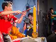 27 JULY 2013 - BANGKOK, THAILAND: A Thai Red Shirt leader lights a candle during a merit making ceremony at the birthday party for Thaksin Shinawatra. The Red Shirts celebrated former Prime Minister Thaksin Shinawatra's 64th birthday with a party at Phibun Prachasan School in Bangkok. They had a Buddhist Merit Making Ceremony, dinner, cake and entertainment. Most of the Red Shirt political elite traveled to Hong Kong for a party with Thaksin. Thaksin, the former Prime Minister, was deposed by a coup in 2006 and subsequently convicted of corruption related crimes. He went into exile rather than go to jail but remains very popular in rural parts of Thailand. His sister, Yingluck Shinawatra is the current Prime Minister and was elected based on her brother's recommendation.     PHOTO BY JACK KURTZ