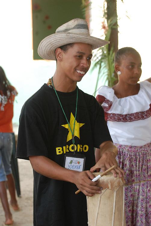 """Joven guia de turismo local de Birongo, pueblo de ¨negros cimarrones y cumbes"""", esclavos huidos de las haciendas mantuanas de la colonia, hoy dedicados al cultivo de Cacao y Chocolate con su fabrica Flor de Birongo, tocan el tambor con ritmos tradicionale de la zona. Edo. Miranda. Venezuela"""