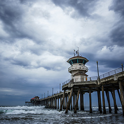 Photo of Huntington Beach Pier and dramatic blue storm clouds. Huntington Beach is a popular Southern California beach city also known as Surf City USA.