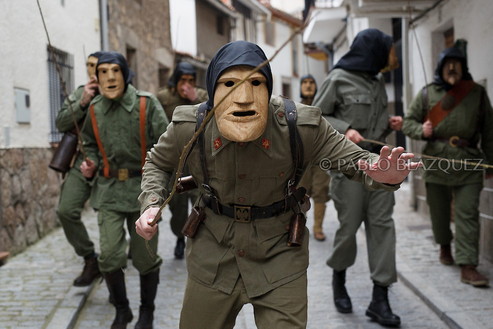 The Machurreros from Pedro Bernardo walk the streets during Carnival on February 6, 2016 in Pedro Bernardo, in Avila province, Spain. The origins of this pagan festival are unknown. The Machurreros wear wood masks, a military dress, black handkerchief, cowbells, and hold wicker stick. The festival disappeared after Dictator Franco forbid carnival festivals in 1937, but it was recently recovered. Before disappearing, male villagers after the military service, used to dress as Machurreros as they run along the streets scaring children and adults with their wicker stick to bring fertility to the land and expel the evil spirits. (© Pablo Blazquez)