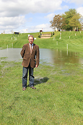 © Licensed to London News Pictures. 30/04/2012. BADMINTON, UNITED KINGDOM. Hugh Thomas, Director of The 2012 Mitsubishi Motors Badminton Horse Trials, stands in front of the Savills Staircase (Fence 23) after announcing that the event will be cancelled due to poor ground conditions. The event, which was a key qualifier for the 2012 London Olympic Games, has been called off because of large areas of standing surface water and worries about the going of the Cross Country track. Photo credit: Mark Chappell/LNP