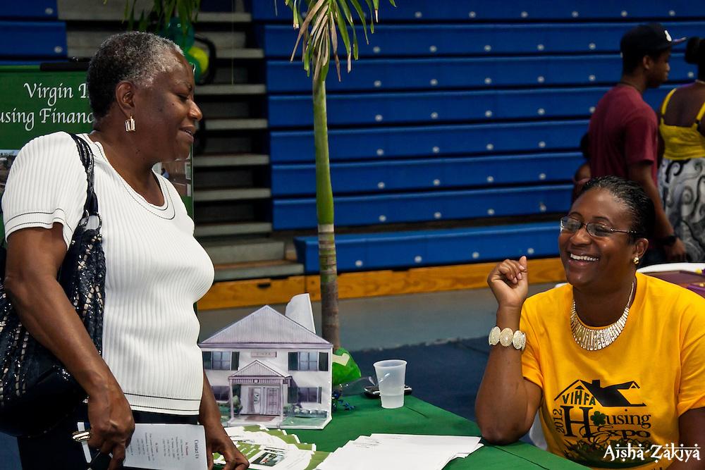 Risa Sasso, right, of the VI Housing Finance Authority greets Dona Bassue at the 2012 VIHFA Housing Expo; Mark C. Marin Center, Antilles School, Saturday, June 30, 2012.  © Aisha-Zakiya Boyd