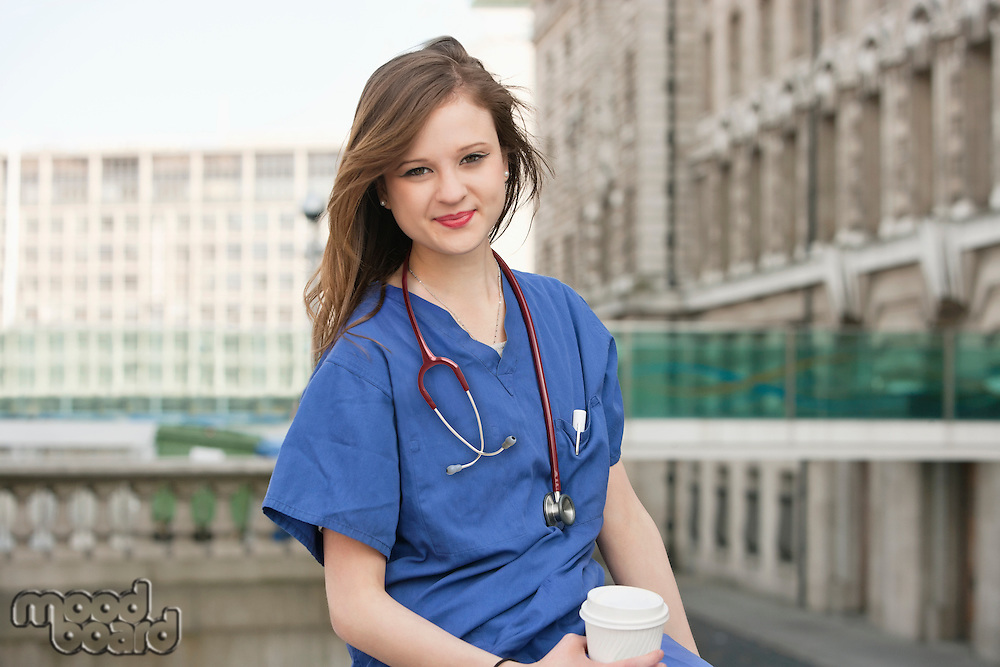 Portrait of a beautiful young female doctor having a coffee break