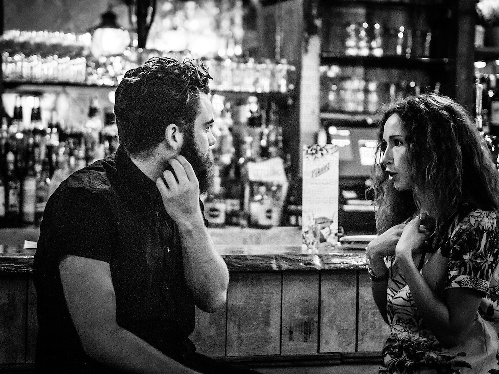 Couple talking sitting at bar