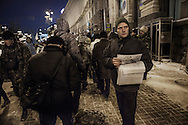 An anti-government protester distributes pamphlets next to one of the barricades defending Maidan Square against police and government supporters on December 10, 2013 in Kiev, Ukraine. Thousands of people have been protesting against the government since a decision by Ukrainian president Viktor Yanukovych to suspend a trade and partnership agreement with the European Union in favor of incentives from Russia was made recently.