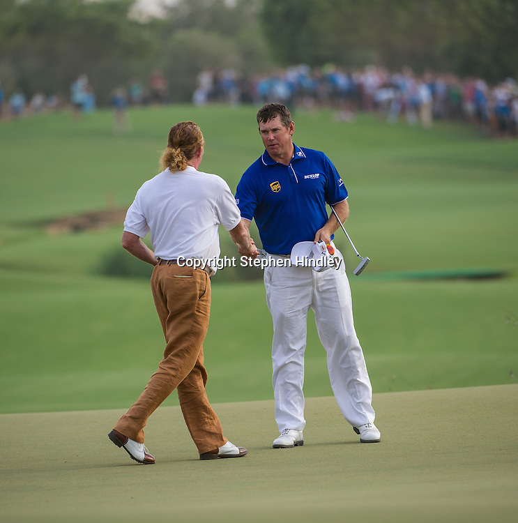 Lee Westwood of England shakes hands with his playing partner for the day, Miguel Angel Jiminez of Spain, at the end of their the final round of the DP World Tour Championship held at the Jumeirah Golf Estates in Dubai, United Arab Emirates, on Sunday, November 17, 2013.  Photo by: Stephen Hindley/SPORTDXB