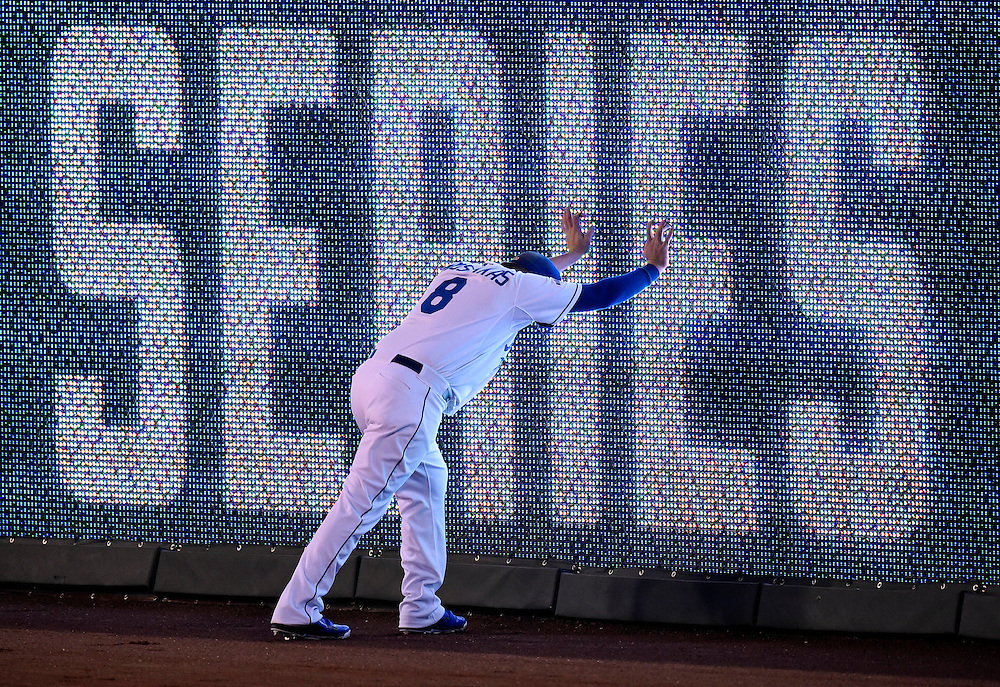 Kansas City Royals third baseman Mike Moustakas stretched against the outfield wall prior to Game 2 against the San Francisco Giants of the World Series on Wednesday, October 22, 2014 at Kauffman Stadium in Kansas City, Mo.