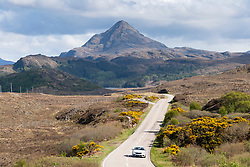 Car driving on the North Coast 500 tourist motoring route in northern Scotland, UK