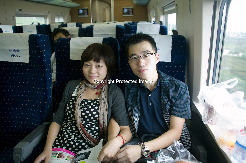 September 11, 2011 :Beijing-Shanghai bullet train : Wang Hailong, 28, (man) and his girlfriend Zhou Hao (23). Of.course, the high speed train is convenient for them, urban middle.class young people, they say. But Mr Wang thinks buying a train ticket.(555 yuans Beijing-Shanghai one way, 64 euros) is a heavy burden for.people who's incomes are on the national average. He says China is.still facing heavy imbalances. Some eastern coastal regions are fast.developing, like the train. But this comparison fails to show other.provinces are still backward and poor.