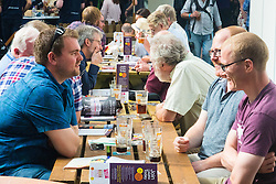 Olympia, London, August 9th 2015. Hundreds of real ale lovers attend the Campaign for Real Ale  Great British Beer Festival at London's Olympia Exhibition Centre, where dozens of independent breweries demonstrate the diversity of British brewed beers. PICTURED: Friends catch up over a pint or two.