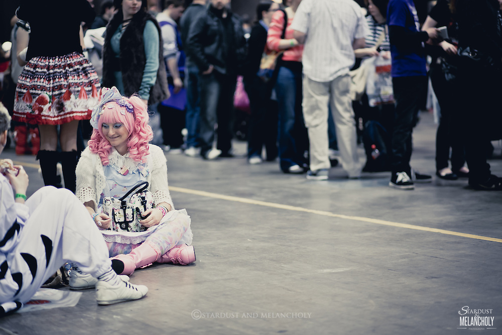 A cosplayer takes a rest while fans line up for autographs in the background, Armageddon Melbourne, 2012