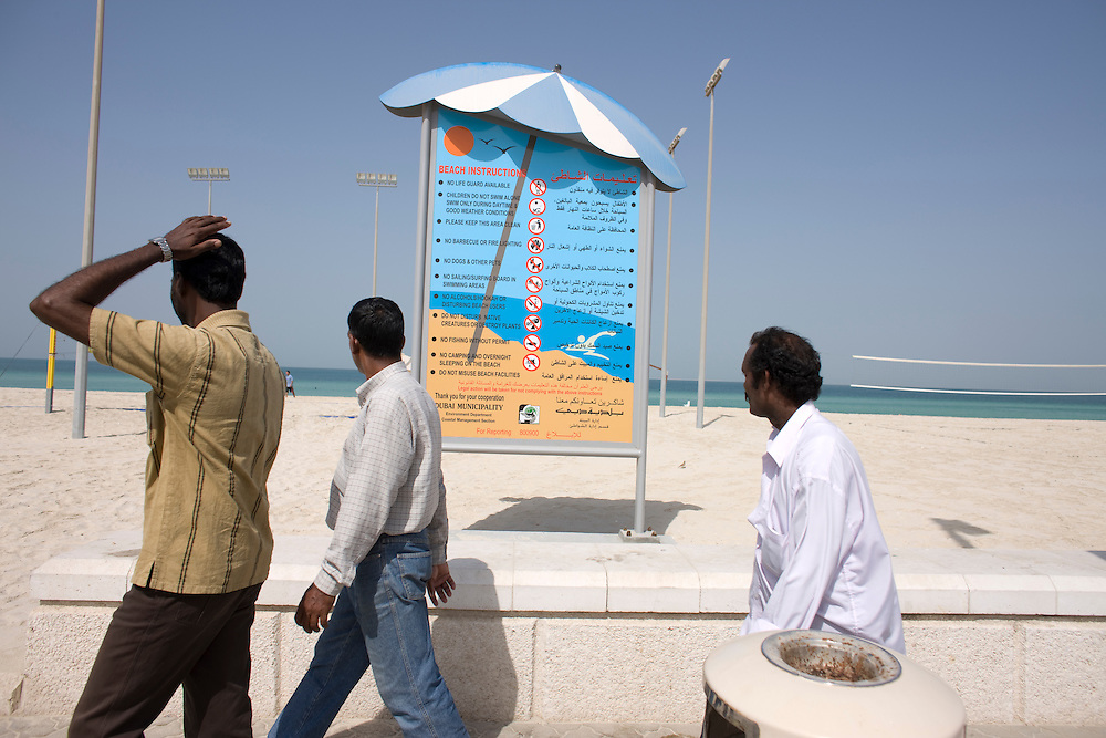 Dubai . Foreign workers walk past rules board along the beach  north west of   Buri Dubai.