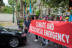 London, UK. 17 July, 2019. Climate activists from Extinction Rebellion block a road to enable a Critical Mass bicycle ride from Waterloo Millennium Green to Hammersmith Town Hall to pass. Activists on the ride on the third day of their 'Summer uprising' have three demands for Hammersmith and Fulham Council: to pass the proposed motion to declare a Climate Emergency; to keep Hammersmith bridge closed to vehicles; and to commit to safer cycling routes.