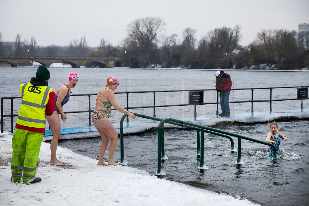 © Licensed to London News Pictures. 02/03/2018. London, UK. Members of the Serpentine Swimming Club brave -1°C water temperatures in the Serpentine in Hyde Park as a workman removes ice from the footpath. The 'Beast from the East' and Storm Emma have brought extreme cold, ice and heavy snow to the UK. Photo credit: Rob Pinney/LNP