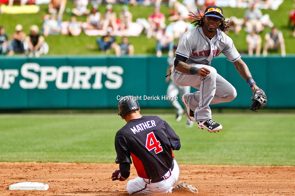 March 5, 2011; Lake Buena Vista, FL, USA; New York Mets shortstop Jose Reyes (7) forces out and jumps over Atlanta Braves outfielder Joe Mather (4) and throws to complete a double play during a spring training exhibition game at Disney Wide World of Sports complex. Mandatory Credit: Derick E. Hingle-US PRESSWIRE